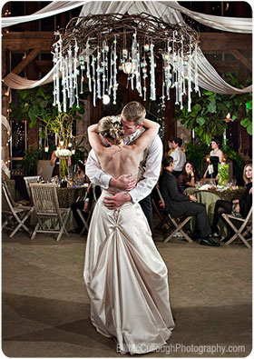 Bride and groom first dance under a chandelier